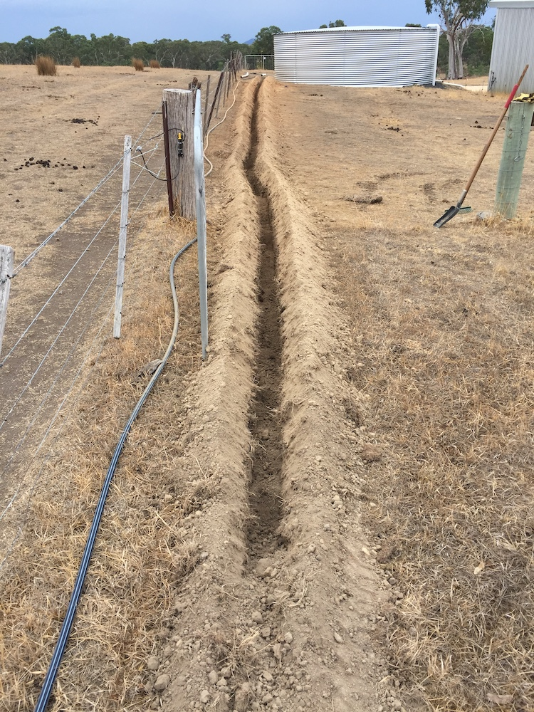 Long trench in hard dry ground for putting pipe in